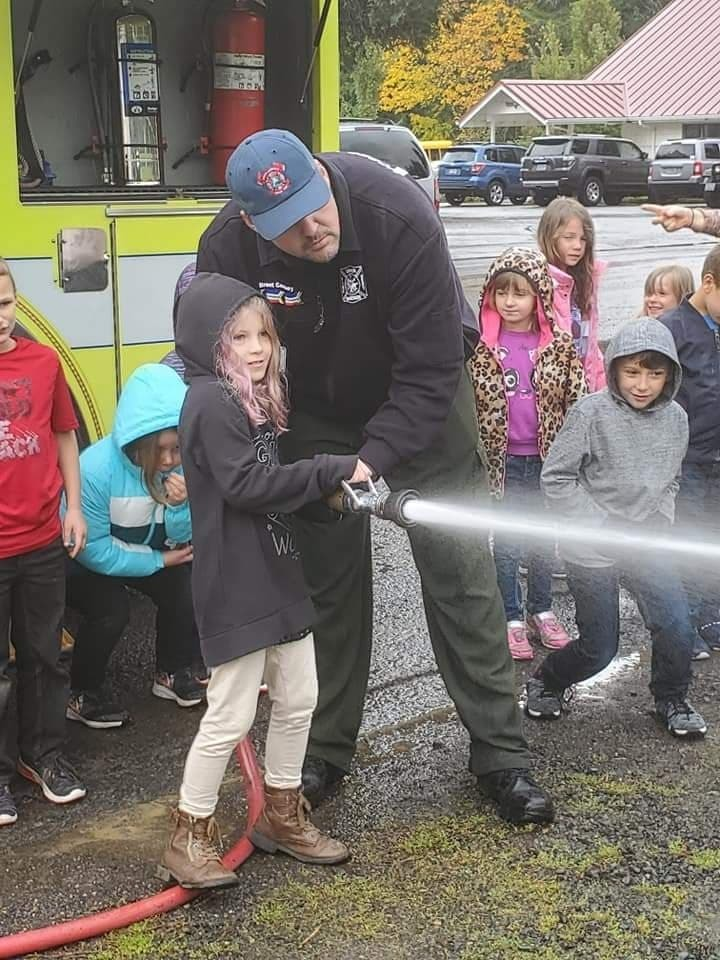 A student uses a firehose during a fire safety demonstration.