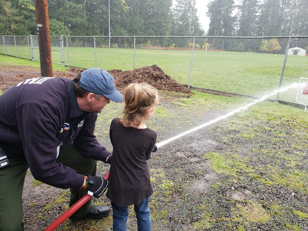 Student uses firehose during fire safety presentation.
