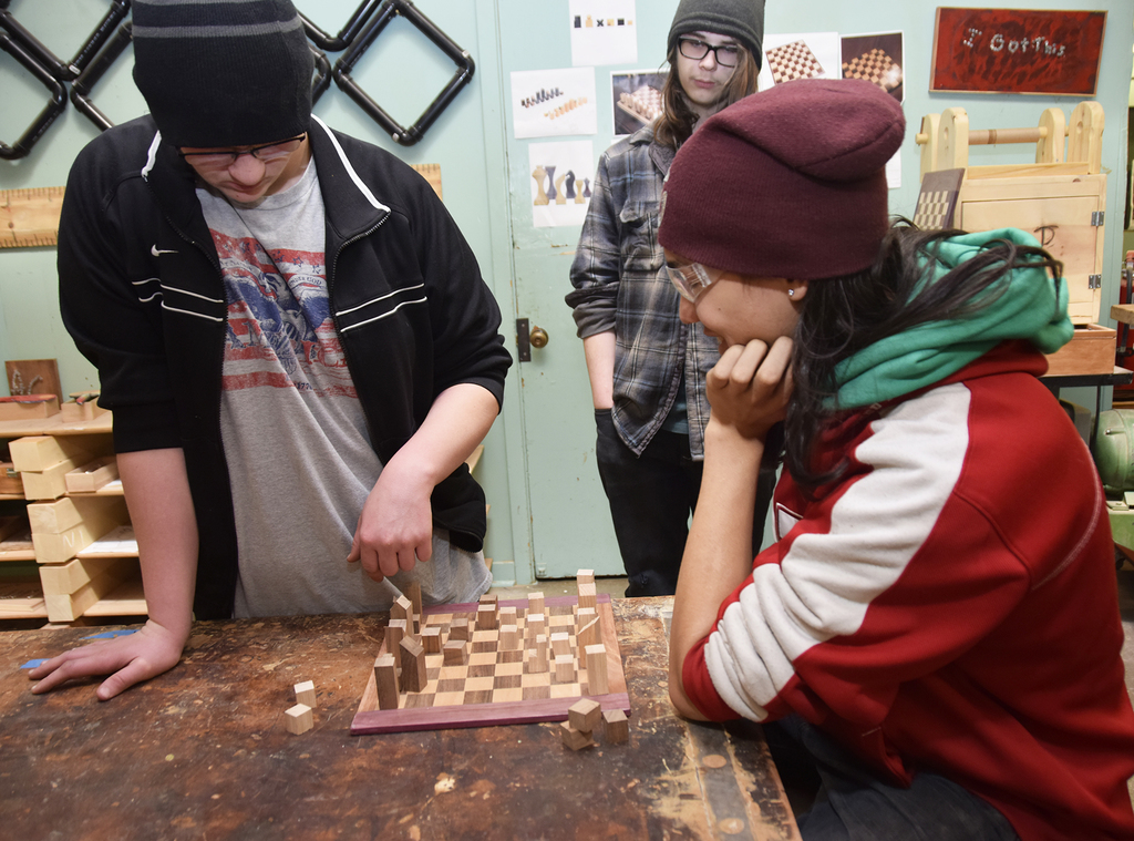 "Joel and Bryce play chess on Joel's original board with ""modern style"" chess pieces."""